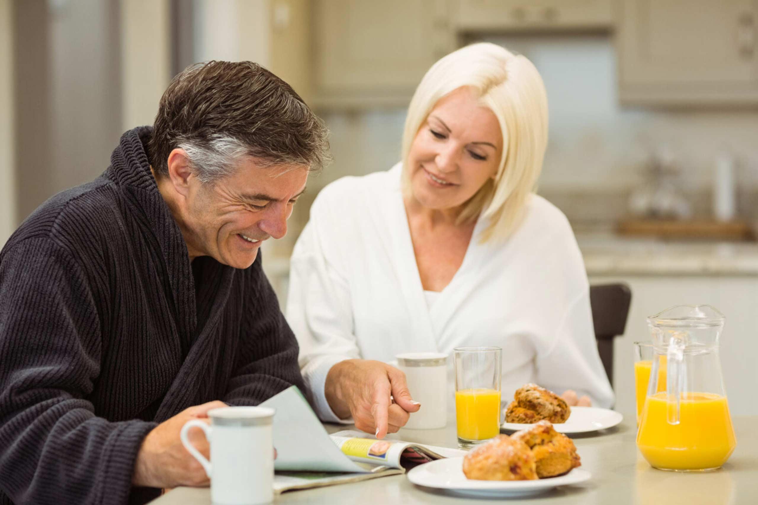 Paar beim Frühstück und Magazin lesen.
